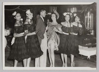 Photograph of a man and five female performers in costume