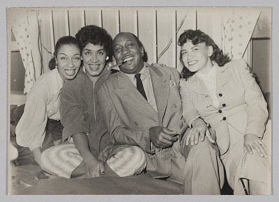 Photograph of Laura Cathrell, a man, and two women at a party