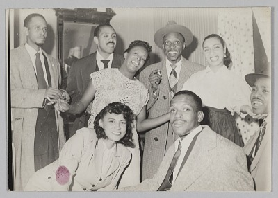 Photograph of a Laura Cathrell and a group of men and women at a party