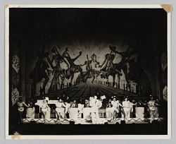 Photograph of a performance with a band, dancers, and singer