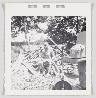 Photographic print of Cliff Jackson sitting next to a pile of scrap wood
