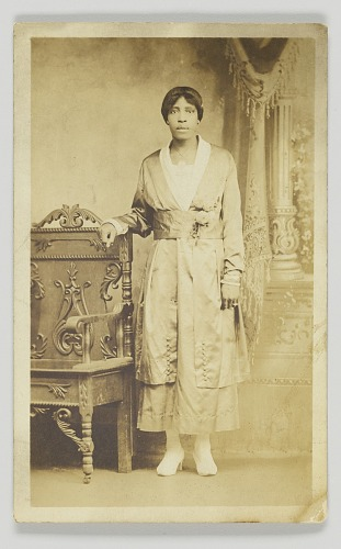 Image for Photographic postcard of a woman standing next to a wooden chair