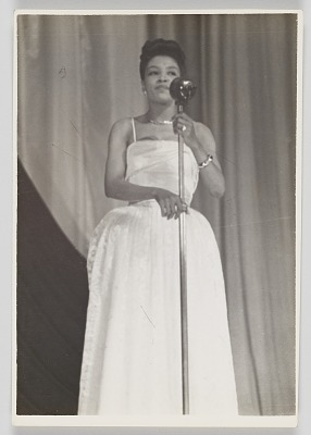 Photographic print of Maxine Sullivan standing at a microphone