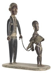 Woodcarving of a slave trader with enslaved female figure