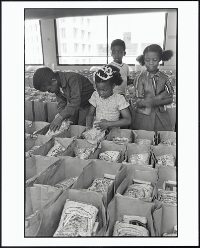 Image for Panther Free Food Program. Children Prepare Bags of Food for Distribution at the Oakland Coliseum at the Black Panther Community Survival Conference, Oakland, California, March 1972