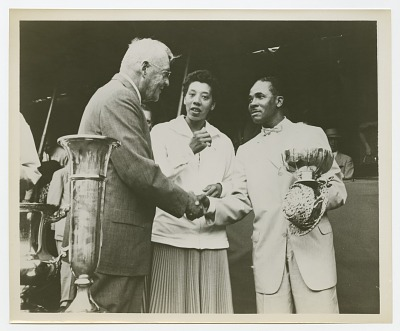 Photograph of Althea Gibson standing next to two men shaking hands