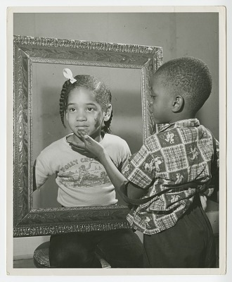 Print of a young girl and boy posing with a picture frame