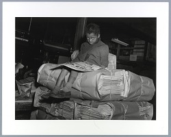 Photograph of girl reading on a pallet of newspapers at the Pittsburgh Courier