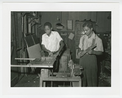 Photographic print of two young men in wood shop