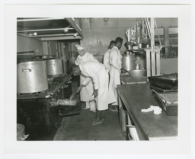 Photographic print of four men cooking in a commerical kitchen