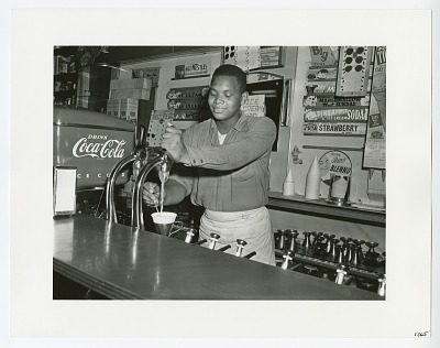 Photographic print of a soda jerk working in a soda shop
