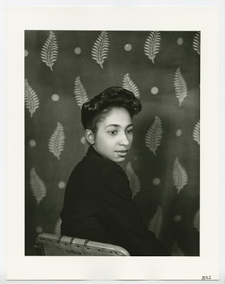 Photographic print of unidentified woman sitting in a Helene Curtis chair