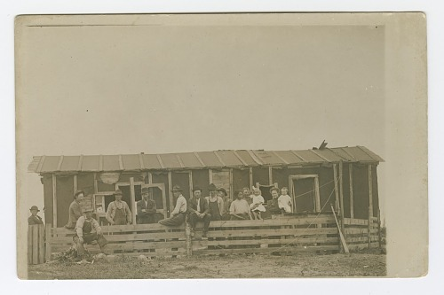 Image for Postcard of men, women, and children outside of a dwelling