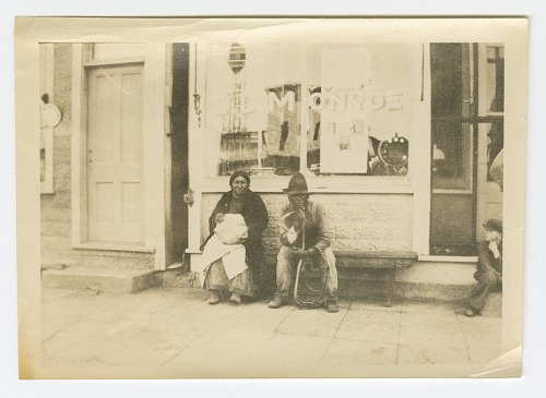 Image for Photograph of a man and woman sitting outside of a storefront