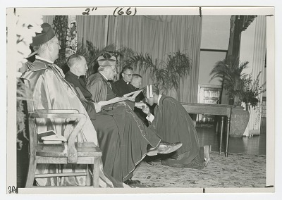 Photograph of a St. Augustine graduate kissing the ring of a Josephite priest