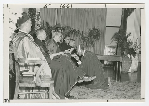 Image for Photograph of a St. Augustine graduate kissing the ring of a Josephite priest