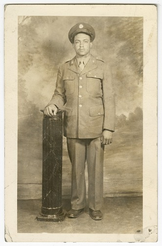 Image for Photograph of a soldier standing next to a pedestal