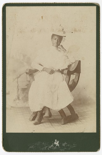 Image for Photograph of a woman wearing a white dress sitting in a chair