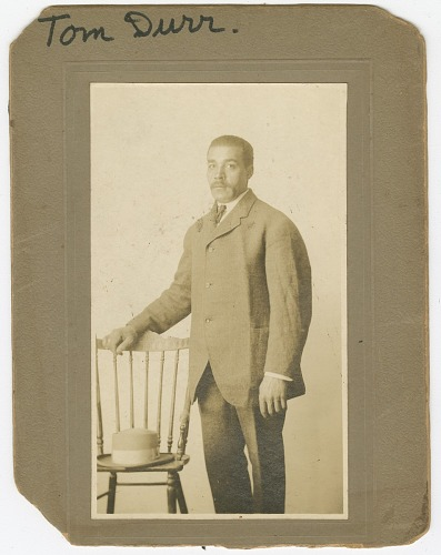 Image for Photograph of Tom Durr standing next to a chair with a hat on it