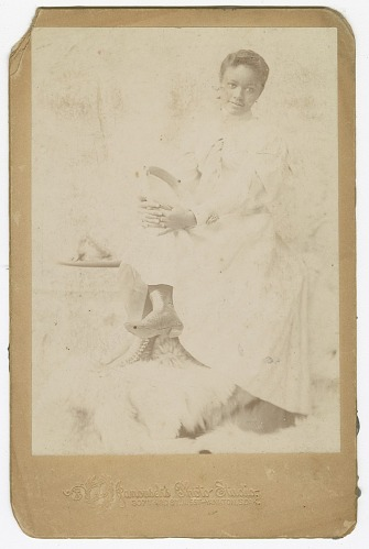 Image for Photograph of a woman sitting with her legs crossed
