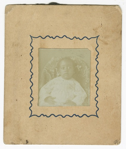Image for Photograph of a baby dressed in white and sitting in a chair