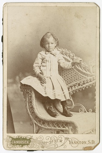 Image for Photograph of a toddler standing on a wicker chair