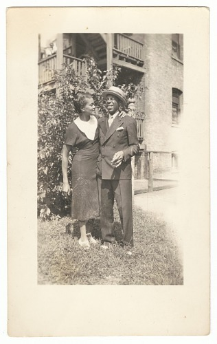 Image for Photographic print of a woman hugging a man in a suit in front of a building