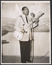 Gelatin silver print of Monk Montgomery singing and playing the guitar