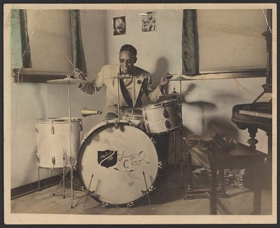 Gelatin silver print of man in sunglasses playing the drums