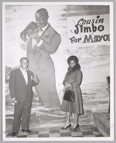 Image for Mr. & Mrs. Louis Armstrong pose in front of his Bop City mural