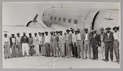 Photographic print of migrant workers in front of a plane