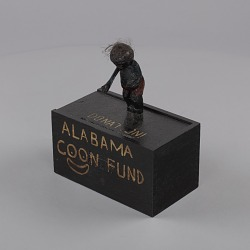 "Donation box and lid with a carving for the ""Alabama Coon Fund"""