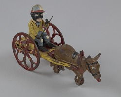 Mechanical toy in the form of a caricatured boy in a mule led racing cart