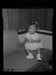 Studio Portrait of a Toddler Girl Sitting on a Sofa