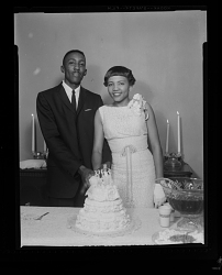Indoor Portrait of a Bride and Groom Standing and Cutting the Wedding Cake