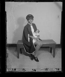 Studio Portrait of a Mother Sitting and Holding her Newborn in her Arms