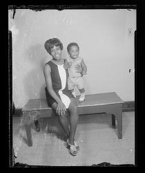Studio Portrait of a Mother Sitting and Child Standing Next to her