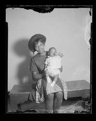Studio Portrait of a Mother Sitting and Holding her Infant