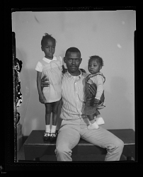 Studio Portrait of a Father Sitting and Two Children Standing