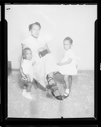 Studio Portrait of a Mother Sitting and her Two Children Standing next to her