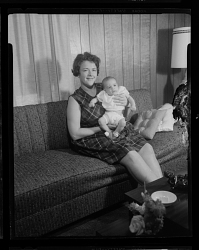 Studio Portrait of a Mother Sitting on a Sofa Holding her Infant