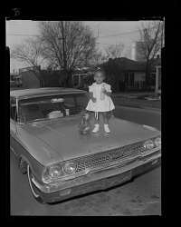 Outdoor Portrait of a Girl Standing on the Hood of a Car