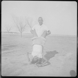 Outdoor Photo of a Man Holding a Woman who is doing a Hand Stand