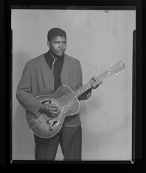 Studio Portrait of a Man Standing Playing Guitar