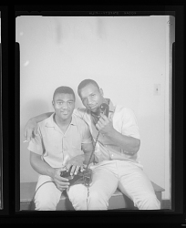 Studio Portrait of Two Men Sitting and Using a Telephone as a Prop