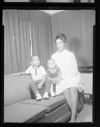 Studio Portrait of a Mother and Two Children Sitting on a Sofa