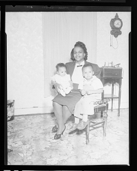 Indoor Portrait of a Mother and Boy Sitting, Mother is Holding Infant