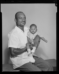 Studio Portrait of a Father Sitting and Holding his Child