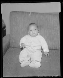 Studio Portrait of an Infant Sitting on a Sofa