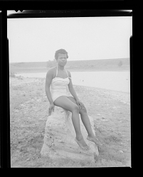 Outdoor Portrait of a Woman Sitting on a Rock Wearing a Bathing Suit